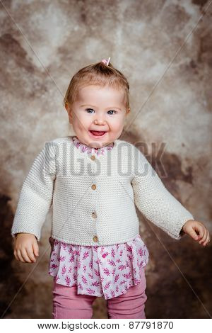 Cute Little Girl With Blond Hair And Grey Eyes Laughs And Dances. Children's Fashion