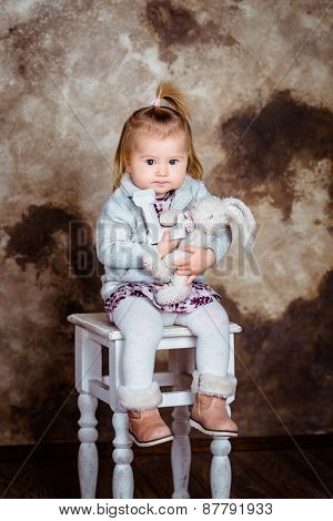 Cute Blond Little Girl Sitting On White Chair And Holding Her Toys. Studio Portrait