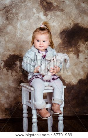 Displeased Blond Little Girl Sitting On White Chair And Holding Her Toys. Studio Portrait