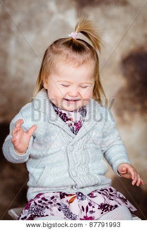 Sweet Little Girl With Blond Hair And Closed Eyes Sitting On White Chair And Laughing