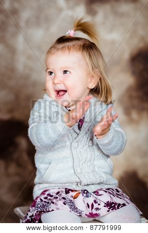 Cute Little Girl With Blond Hair Sitting On Chair, Laughing And Clapping Her Hands. Studio Portrait