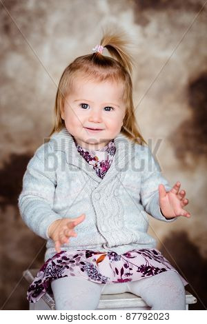 Sweet Smiling Little Girl With Blond Hair Sitting On Chair And Clapping Her Hands