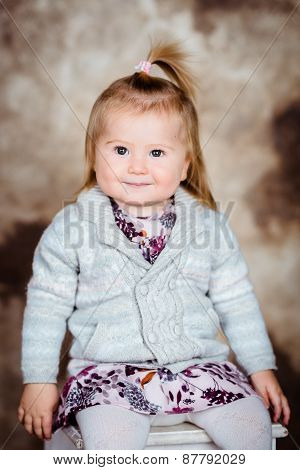 Adorable Little Girl With Blond Hair Sitting On White Chair And Smiling