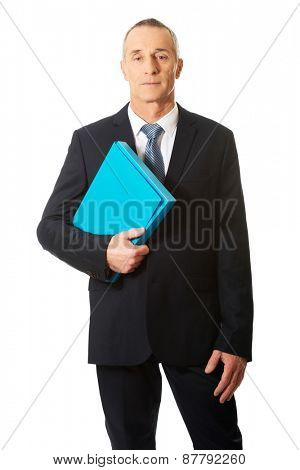 Smiling mature businessman holding a binder.