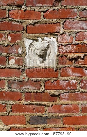 Red brick wall with gargoyle