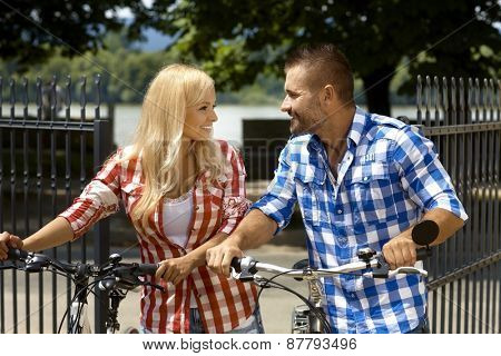 Happy casual couple on vacation with bicycle in outdoor park. Attractive blonde woman and handsome stubbly man. Smiling, sport activity, summer.