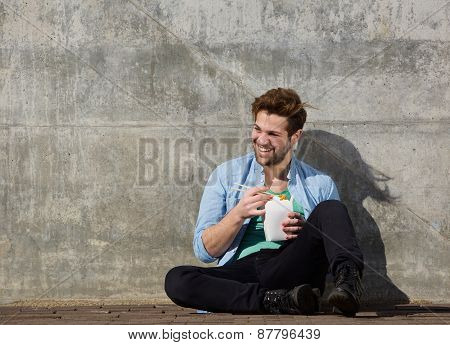 Cheerful young man eating chinese take away food with chopsticks