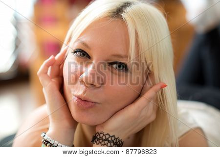 Young Blond Woman Is Air-kissing
