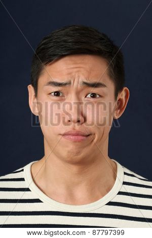 Disgusted young Asian man looking at camera