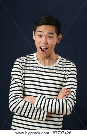 Laughing young Asian man with crossed hands looking at camera
