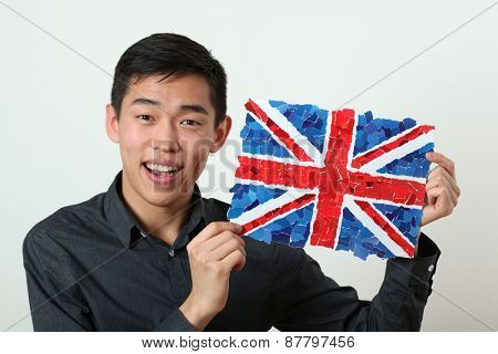 Young Asian student showing UK national flag and looking at camera