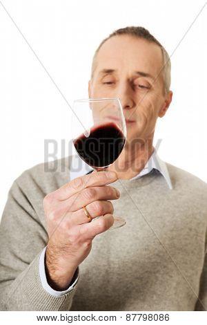 Smiling mature man tasting red wine.