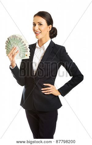 Happy businesswoman holding a clip of polish money.
