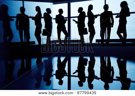 Interacting business partners standing by window