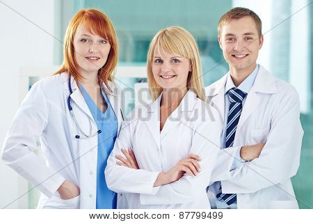Happy young colleagues in white coats looking at camera