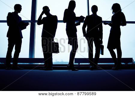 Several business partners having meeting by office window