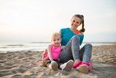 foto of mother baby nature  - Happy healthy mother and baby girl sitting on beach in the evening - JPG