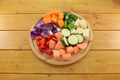 stock photo of parsnips  - Selection of chopped vegetables on a wooden chopping board  - JPG