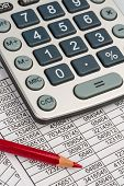 picture of depreciation  - a calculator is on a balance sheet numbers are statistics - JPG