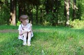 image of eat grass  - Pretty happy girl sits on green grass in forest and eats at sunny day - JPG