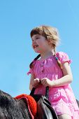 picture of saddle-horse  - Little beautiful girl in pink dress sits in saddle on brown horse - JPG