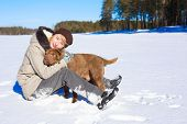 stock photo of shar pei  - Woman hugging her shar pei while sitting on the snowy field near a pinery on a sunny day - JPG