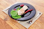 image of kale  - fresh roast turkey meat steak fillet with red hot pepper and green lettuce salad kale on black plate over wooden table with knife and fork - JPG