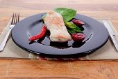 picture of kale  - fresh roast turkey meat steak fillet with red hot pepper and green lettuce salad kale on black plate over wooden table with knife and fork - JPG