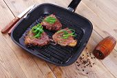 image of bloody  - fresh grilled bloody beef steaks on black grill plate on wood - JPG