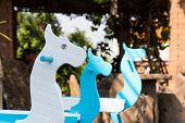 stock photo of paint horse  - blue and white painted rocking horse in the garden - JPG