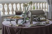 stock photo of chafing  - catering table set with appetizers and snacks - JPG