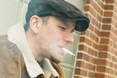 foto of newsboy  - Cool guy in aviator jacket and newsie cap relaxes against a glass wall and enjoys his cigarette - JPG