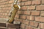 foto of sax  - Lone old saxophone leans against brick wall outside abandoned jazz club - JPG