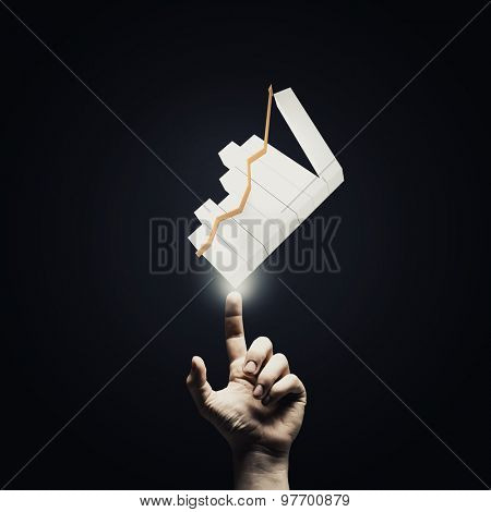 Human hand pointing with finger at growing graph
