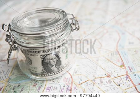 Dollars magnifying glass passport sunglasses and a world map