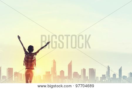 Rear view of girl with hands up facing sunrise abone city