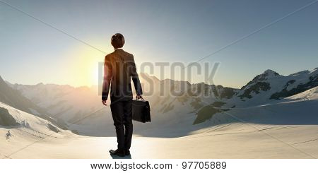 Rear view of businessman look at sunrise above mountain