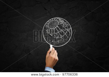 Close up of hand drawing globe on blackboard