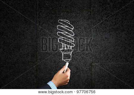 Close up of hand drawing light bulb with chalk