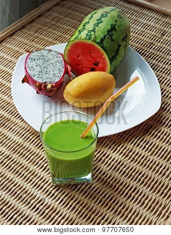 Blended Green Smoothie And Sliced Tropical Fruits
