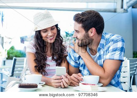 Cute couple sitting in cafe looking at smartphone on a sunny day