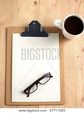 Glasses, a cup of coffee and business documents