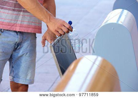 Man Hand Putting Plastic Bottle In Recycling Bin