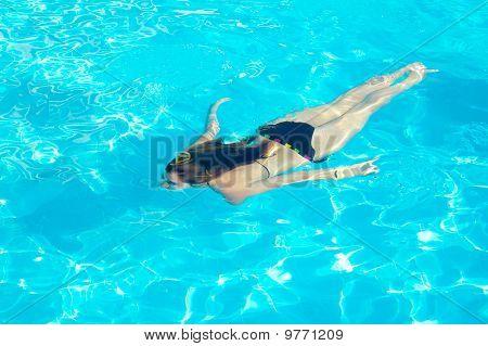 Joven nadar bajo el agua en la piscina