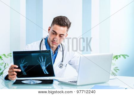 Handsome Doctor Reviewing X-rays At Desk.