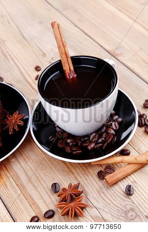 sweet dessert : black coffee and chocolate cake with cinnamon , coffee beans, and anise star on wooden table