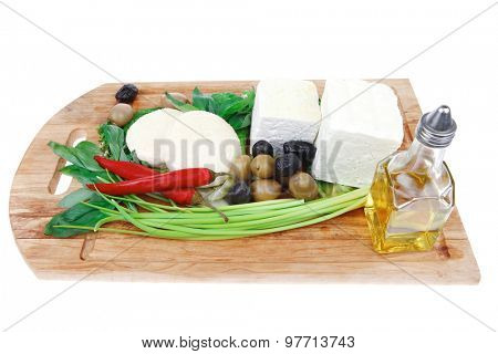 diet food : greek feta white cheese served on wooden plate with basil leaves red hot pepper , black and green olives , and olive oil isolated over white background