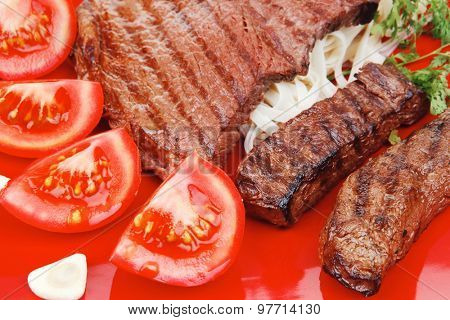 italian cuisine : grilled steak with pasta and tomatoes on red plate isolated over white background