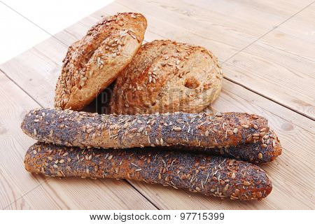 delicacy french rye breads and baguettes topped with sunflower and poppy seeds over wooden table