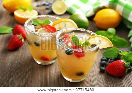 Glasses of berries juice with lemon on wooden table, closeup